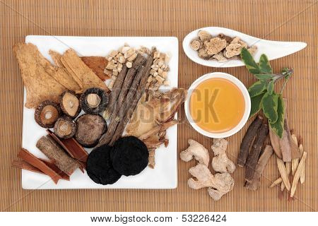 Traditional chinese herbal medicine selection with honey over bamboo.