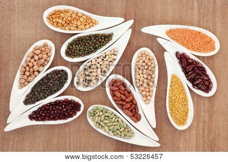 Dried pulses selection in white porcelain dishes over papyrus background.