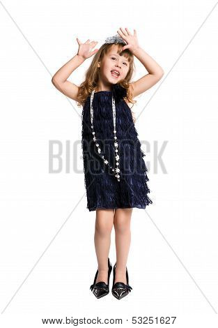fashionista little tries big shoes on a white background