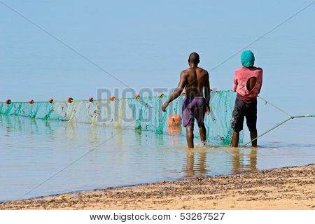 Mozambican fishermen pulling a fishing net from the water