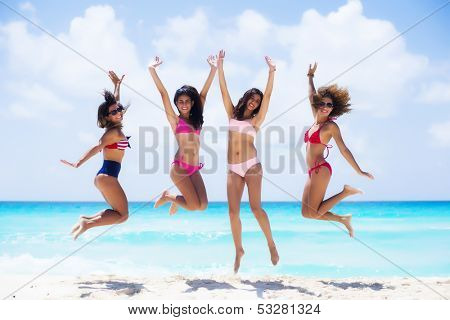 Group of friends jumping at a tropical beach