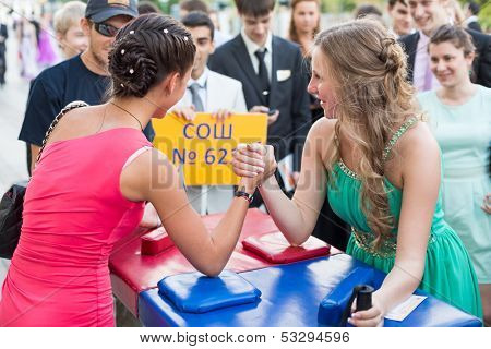 MOSCOW - JUN 23: The girls graduates in beautiful dresses are arm wrestling on the street on June 23, 2013 in Moscow, Russia.