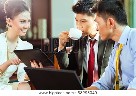 Three Asian Chinese office people or businessmen and businesswoman having a business meeting in a hotel lobby discussing documents on a tablet computer while drinking coffee