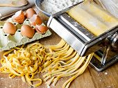stock photo of pasta  - Fresh pasta cutting in machine - JPG