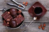 foto of melchior  - Bowl with chocolate nuts nutcracker and coffee on a gray wooden background - JPG
