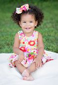 stock photo of mulatto  - Hispanic toddler with an afro hairstyle sitting on the park - JPG