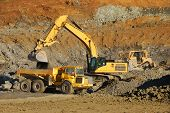 stock photo of track-hoe  - Excavation equipment moving the blasted rock during a large coonstruction project in Roseburg Oregon - JPG