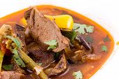 pic of stew pot  - Stewed meat with a broth in a white plate close up