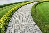 stock photo of cobblestone  - The Stone block walk path in the park with green grass background - JPG