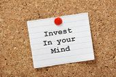 picture of mantra  - Invest in Your Mind typed onto a lined paper note pinned to a cork notice board - JPG