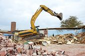 stock photo of backhoe  - A large backhoe demolishes an old building - JPG