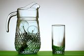 pic of tumblers  - Glass jug of light bulbs and glass on green tablecloth - JPG