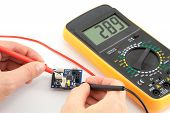 stock photo of ohm  - Repair of electronics with digital multimeter in the white background - JPG