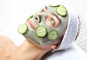 stock photo of cucumber  - woman relaxes in the mask with green clay and cucumber - JPG