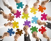 foto of merge  - Concept of teamwork and integration with businessman holding colorful puzzle - JPG