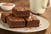 stock photo of brownie  - Freshly baked brownie pieces on a plate with cup in the back (Selective Focus Focus on the left front part of the upper brownie)