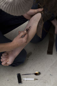 stock photo of opiate  - Man giving a dose of heroin to his girlfriend - JPG