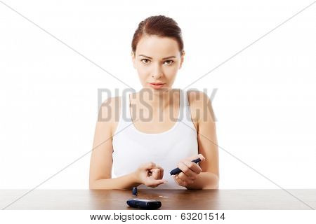 Young beautiful woman doing sugar level test.  Over white background.