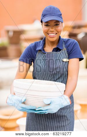pretty afro american hardware store worker holding flower pot