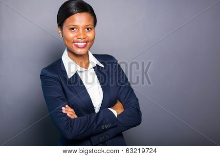 happy african american woman with arms crossed against black background
