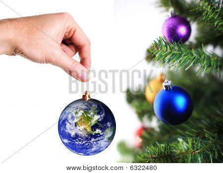 Mão pendurado em terra decoração na árvore de Natal