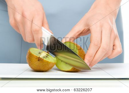 Cook is chopping kiwifruit, closeup shoot, isolated over white