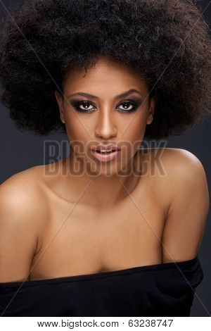 Beautiful glamorous Afro-American woman with a frizzy afro hairdo and bare shoulders