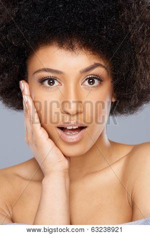 Beautiful surprised African American woman looking at the camera with a raised eyebrow and shocked expression, close up face portrait