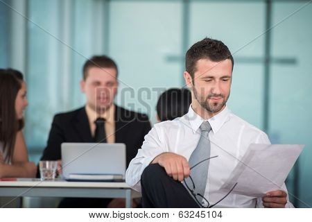 Business man reading papers in modern office