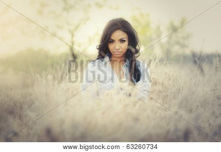 Beautiful young woman wearing denim top and short bottoms in ethereal Arizona dry desert landscape.