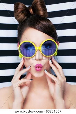 Attractive surprised young woman wearing sunglasses on striped background, beauty and fashion concept