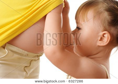 Daughter Looking At Pregnant Mother's Belly
