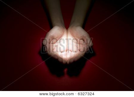 Child Holding Light On Red Background