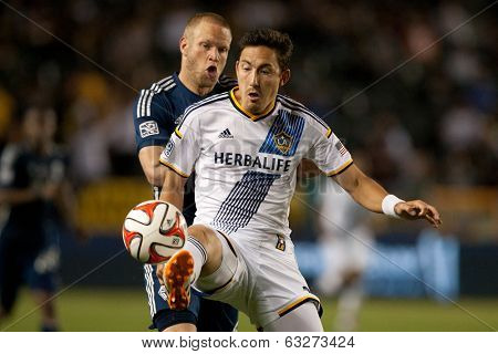 CARSON, CA - APRIL 12: Los Angeles Galaxy M Stefan Ishizaki #24 & Vancouver Whitecaps D Jay DeMerit #6 during the MLS game between the Los Angeles Galaxy & the Vancouver Whitecaps on April 12th 2014