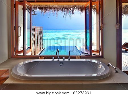 Luxury beautiful interior design on beach resort, window view from bathroom on clear blue sea, summer vacation on Maldives