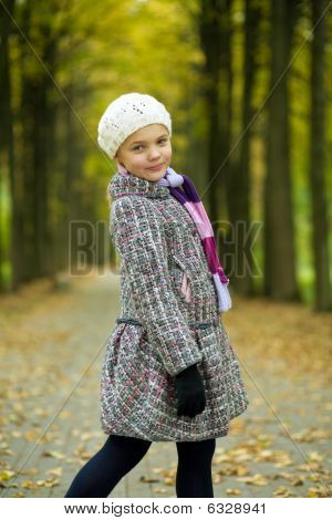 smiling happy young blonde girl in modern coat standing turned backwards