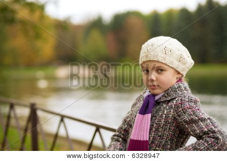 dreaming nice girl in white beret standing near river bank
