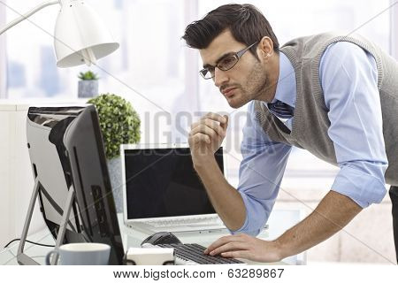 Young businessman working with computer in bright office.