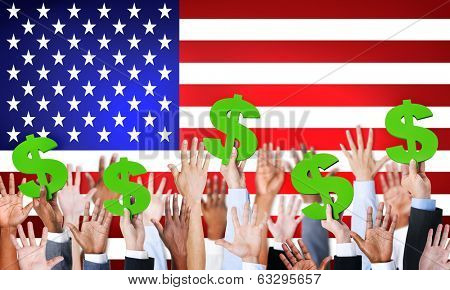 Multi-Ethnic Hands Holding Dollar Signs With Flag Of USA For The Background.