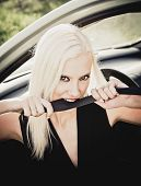 stock photo of love bite  - Sexy blonde woman sitting in a car and biting the safety belt - JPG