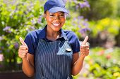 cheerful african female nursery worker with thumbs up