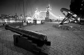 Cannon and Tower Bridge at night at St. Katherine Dock in London.