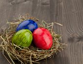 Easter Eggs In Hay Nest On Dark Wood