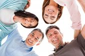 foto of huddle  - Group Of Happy People Making Huddle Over White Background - JPG