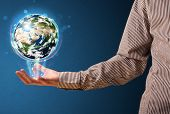 Young businessman holding in his hand a glowing earth globe, Elements of this image furnished by NAS