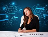 Young businesswoman doing paperwork with futuristic background