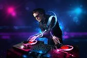 stock photo of disc jockey  - Young disc jockey playing music with electro light effects and lights - JPG