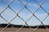 image of chain link fence  - Close up of a chain linked fence with a blurred blue sky landscape on the background - JPG