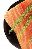 raw fresh uncooked salmon red fish fillet on black plate with rosemary twig isolated over white back
