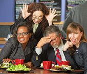 stock photo of embarrassing  - Embarrassed man with coworkers making faces in cafe - JPG